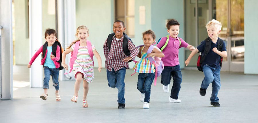 group of children running towards the camera at school